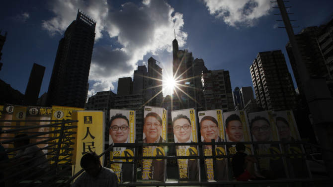 In this photo taken Sunday, Sept. 2, 2012, promotional posters of Legislative Council election candidates Christopher Lau Ka-hung, left, and Shiu Yeuk-yuen, second left, from the pro-democracy People Power are displayed at a park in Hong Kong. China's territory of Hong Kong has a high degree of autonomy, freedom of the press and limited democracy, but its politics remains highly constrained by Beijing's wariness over threats to its authority.  (AP Photo/Kin Cheung)