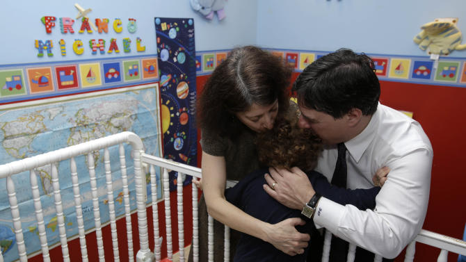 "In this Jan. 30, 2013 photo, Drew and Frances Pardus-Abbadessa hug their son, Pavol, 1, in the nursery originally intended for a child they have been trying to adopt for five years, at their apartment in New York.  The boy's Russian name is Vladimir,  but they hope one day to be able to name him Franco Michael ,  the name still displayed on the wall. The Pardus-Abbadessa family were among a group initially known as the ""Kyrgyz 65"" - Americans who were in the process of adopting 65 orphans from the Central Asian republic when it suspended international adoptions in 2008 due to allegations of fraud.  Some of the children were placed in domestic adoptions, and last summer nine of the remaining children finally were allowed to go to America. The Pardus-Abbadessas are now among 16 U.S. families still waiting. (AP Photo/Seth Wenig)"