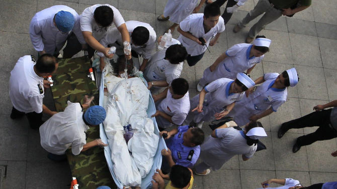 Medical staff move a severely burnt victim of an explosion at an eastern Chinese automotive parts factory from a hospital in the city of Kunshan, Jiangsu province, Saturday, Aug. 2, 2014 to a Shanghai hospital which is better equipped to handle severe burns. Dozens of people were killed Saturday by the explosion at the factory that supplies General Motors, state media reported. (AP Photo) CHINA OUT