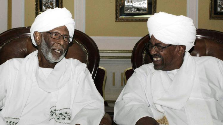 Bashir talks with Turabi during an official meeting in Khartoum
