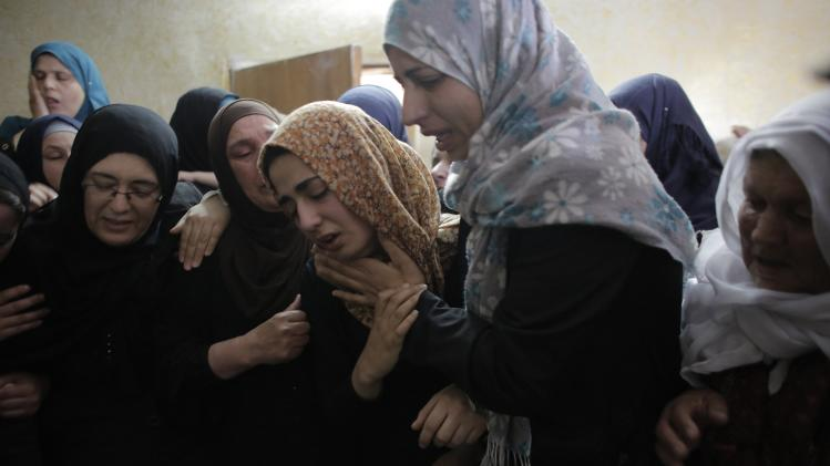 Relatives of Palestinian boy Nasri Mahmoud Qaqatqa, whom medics said was killed by Israeli troops during clashes on Friday night, mourn during his funeral in the West Bank village of Beit Fajjar near Bethlehem