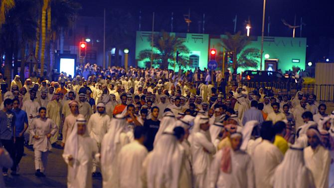 Kuwaiti men walk near Erada Square during a demonstration in Kuwait City on Sunday, October 21, 2012. Several thousand protestors from opposition groups, Bedouin tribes and former MPs gathered in different points of Kuwait City to demonstrate against the Government's amendment of the country electoral law.(AP Photo/Gustavo Ferrari)