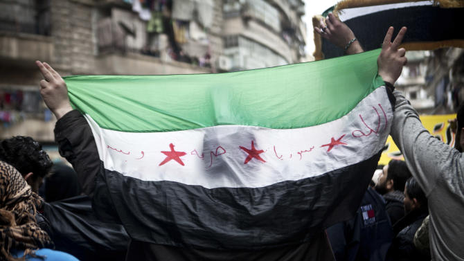 A Syrian carries a revolution flag during a Friday protest in Aleppo, Syria, where young people and children sang songs against Bashar Assad and the Syrian regime, Friday, Dec. 21, 2012.(AP Photo/Virginie Nguyen Hoang)
