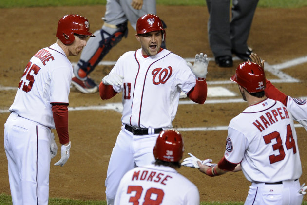 Washington Nationals&#39; Ryan Zimmerman, center, high-fives teammates Adam LaRoche, left, Michael Morse and Bryce Harper after hitting a two-run home run in the first inning of Game 5 of the National League division baseball series against the St. Louis Cardinals on Friday, Oct. 12, 2012, in Washington. Harper scored on the homer. (AP Photo/Nick Wass)