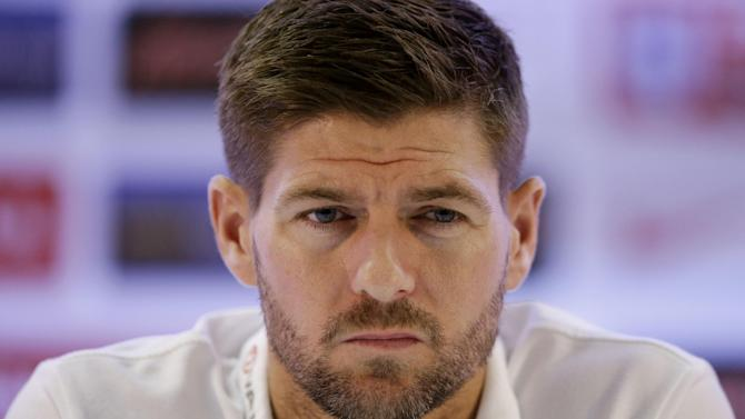 In this Sunday, June 22, 2014 file photo, England national soccer team captain Steven Gerrard listens as head coach Roy Hodgson speaks during a press conference after a squad training session that was closed to the media for the 2014 soccer World Cup at the Urca military base in Rio de Janeiro, Brazil. England captain Steven Gerrard announced his retirement from international football on Monday, July 21, 2014. The 34-year-old Liverpool midfielder made 114 appearances for England over 14 years