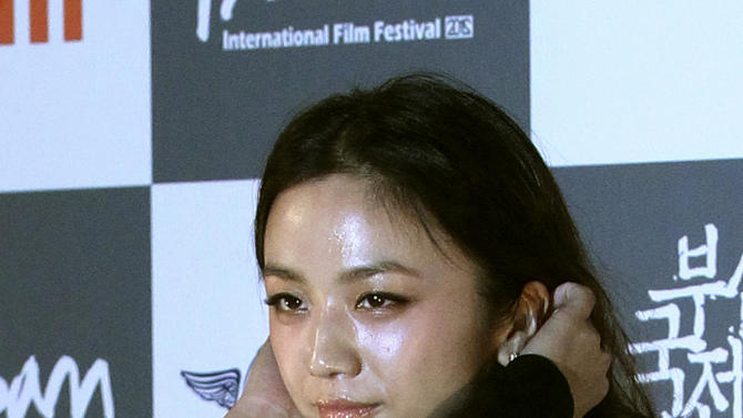 """FILE - In this Oct. 4, 2012 file photo, Chinese actress Tang Wei adjusts her hair to pose for photographers during the opening ceremony of the Busan International Film Festival in Busan, South Korea. """"Lust, Caution"""" actress Tang fell victim to a $35,000 fraud after being persuaded over the phone to wire money to a suspect, state media reported Sunday, Jan. 12, 2014. Citing local police, the official Xinhua News Agency reported that Tang was filming in Shanghai on Saturday afternoon when she received a phone call and was persuaded to go to a bank and wire the 210,000 yuan ($35,000). (AP Photo/Ahn Young-joon, File)"""