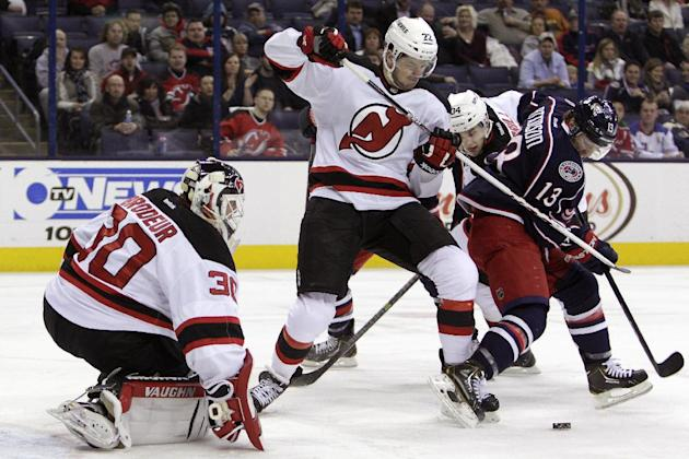 New Jersey Devils' Martin Broseur, left, makes a save as teammate Eric Gelinas, center, and Columbus Blue Jackets' Cam Atkinson fight for a loose puck during the second period of an NHL hockey