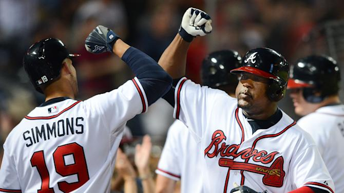Atlanta Braves third baseman Juan Uribe is congratulated by shortstop Andrelton Simmons (19) after Uribe's go-ahead home run in the seventh inning of a baseball game against the Philadelphia Phillies Friday, July 3, 2015, in Atlanta. The Braves won 2-1. (AP Photo/Jon Barash)