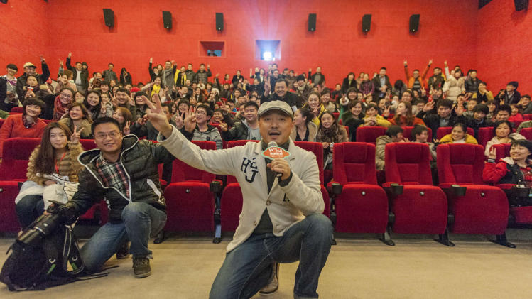"In this Dec. 20, 2012 photo, movie director and actor Xu Zheng, center, speaks with fans at a movie theatre to promote his latest movie ""Lost in Thailand"" in southwestern China's Chongqing city. The low-budget, domestically produced comedy has unexpectedly become the highest-grossing Chinese film to date. (AP Photo)  CHINA OUT"