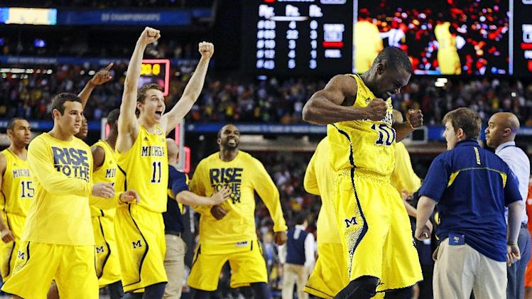 Michigan players including Tim Hardaway Jr., right, and Nik Stauskas (11) celebrate after defeating Syracuse in their NCAA Final Four tournament college basketball semifinal game on Saturday, April 6, 2013, in Atlanta. Michigan won 61-56. (AP Photo/Charlie Neibergall)