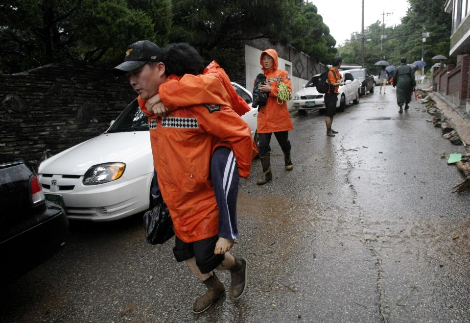 A South Korean firefighter carries an injured woman on his back after a landslide caused by heavy rains in Seoul, South Korea, Wednesday, July 27, 2011. A quick blast of heavy rain sent landslides barreling through South Korea's capital and a northern town Wednesday. (AP Photo/Ahn Young-joon)
