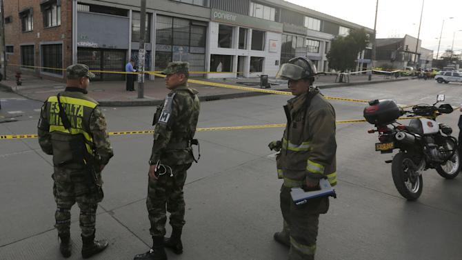 Soldiers and a firefighter stand close to the site where an explosion occurred at the office of the Porvenir pension fund in downtown Bogota