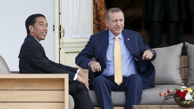 Indonesia's President Joko Widodo and Turkey's President Recep Tayyip Erdogan sit on the balcony at the presidential palace in Jakarta, Indonesia