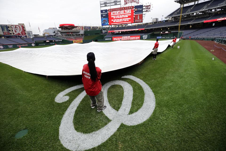 The grounds crew spreads the tarp over the infield at Nationals Park after the baseball game between the Washington Nationals and the Los Angeles Dodgers was postponed because of rain on Tuesday, Sept. 18, 2012, in Washington. The clubs will make up the game on Wednesday as part of a doubleheader. (AP Photo/Alex Brandon)