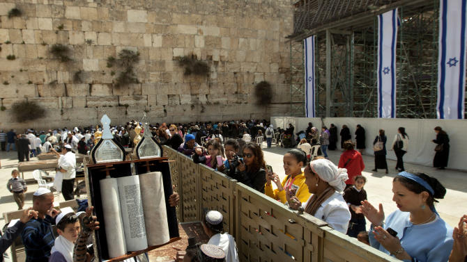 A man holds up a Torah scroll as women stand across a fence at the Western Wall, the holiest site where Jews can pray in Jerusalem's old city, Wednesday, April 10, 2013.  The rabbi of Judaism's holiest prayer site has backed a proposal to establish a prayer section for mixed-gender worship, a groundbreaking motion that could end a decades-old fight against Orthodox monopoly of the area. (AP Photo/Sebastian Scheiner)