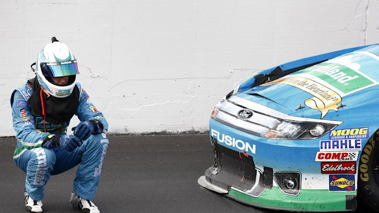 Aric Almirola waits for help following a crash during a NASCAR Sprint Cup Series auto race at Kansas Speedway in Kansas City, Kan., Sunday, Oct. 21, 2012. (AP Photo/Colin E. Braley)