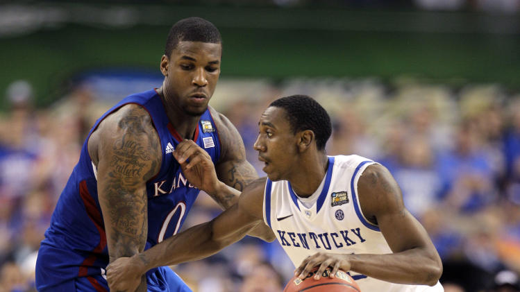 Kentucky guard Marquis Teague (25) tries to dribble around Kansas forward Thomas Robinson (0) during the second half of the NCAA Final Four tournament college basketball championship game Monday, April 2, 2012, in New Orleans. (AP Photo/Mark Humphrey)