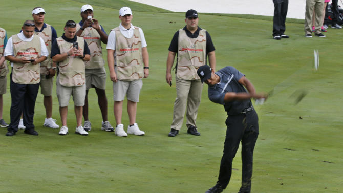 Tiger Woods hits up to the green on the 15th hole as military caddies watch during the pro-am for the Quicken Loans National Golf tournament at the Robert Trent Jones Golf Club in Gainesville, Va., Wednesday, July 29, 2015. The 15th hole was designated the Military Appreciation Hole.  (AP Photo/Steve Helber)