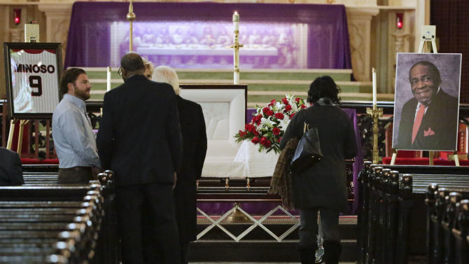 """Mourners pass by the casket of former Chicago White Sox great Minnie Minoso on Friday, March 6, 2015, to pay their respects during a public visitation at Holy Family Church in Chicago.  The Havana native and major league baseball's first black Latino star died Sunday, March 1. He was believed to be 90. Known as the """"Cuban Comet,"""" Minoso was part of a wave of black players who transformed the game. (AP Photo/M. Spencer Green)"""