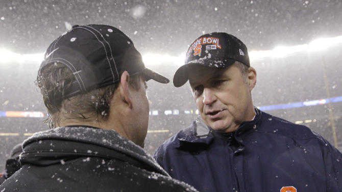Syracuse coach Doug Marone, right, greets West Virginia coach Dana Holgorsen after Syracuse defeated West Virginia 38-14 in the Pinstripe Bowl NCAA college football game at Yankee Stadium in New York, Saturday, Dec. 29, 2012. (AP Photo/Kathy Willens)