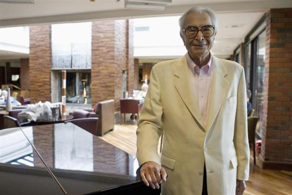 Dave Brubeck stands next to a piano in Monterey