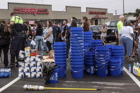 Volunteers gather in a shopping center parking lot before dispersing to help with flood relief efforts in San Marcos, Texas