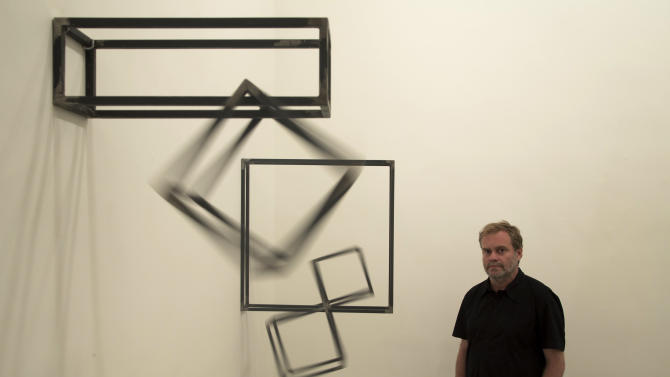 In this Aug. 30, 2012 photo, Brazilian sculptor Raul Mourao poses for a photo next to his work, as it moves while hanging on exhibit at the Lurixs contemporary art gallery in Rio de Janeiro, Brazil.  Mourao has watched Rio's art scene establish itself in the last two decades. When he started, there weren't more than a dozen books out on Brazilian art in general. Now there are dozens of exhibits in Rio at any given time, as well as an established culture of publicly financed displays.  (AP Photo/Felipe Dana)