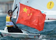 Xu Lijia of China waves her national flag as she celebrates her gold medal in the women's Laser class in the Olympic sailing regatta at Weymouth on Monday
