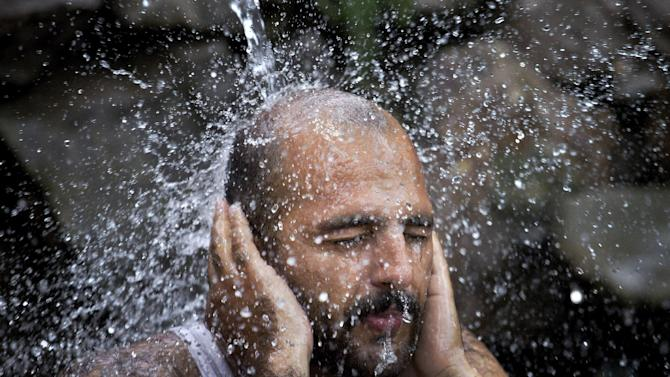 A Pakistani man cools himself off under a water supply line, after temperature reached 39 degrees Celsius (102.2 Fahrenheit), in Islamabad, Pakistan, Sunday, July 5, 2015. Many cities in Pakistan are facing heat wave conditions with temperatures reaching up to 47 degrees Celsius (116.6 Fahrenheit) in some places. (AP Photo/Anjum Naveed)