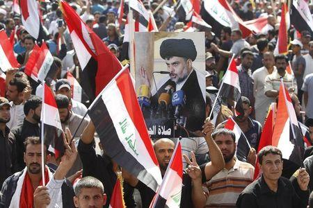 Demonstrator holds a picture of Shi'ite cleric Moqtada al-Sadr during a protest in Baghdad