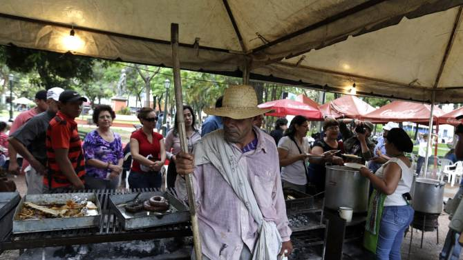 "Man stands in front of a queue of people waiting to receive servings of a traditional dish called ""yopara"" during Karai Octubre celebrations in Asuncion"