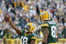 Green Bay Packers' Randall Cobb celebrates a touchdown catch in front of New York Jets' Kyle Wilson (20) during the first half of an NFL football game Sunday, Sept. 14, 2014, in Green Bay, Wis. (AP Photo/Tom Lynn)