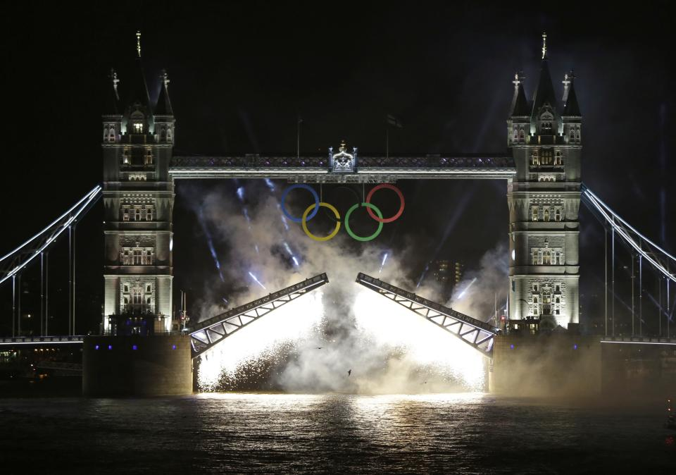 Smoke from fireworks surrounds the iconic Tower Bridge over the River Thames in central London, decorated with Olympic rings, during the Opening Ceremony at the 2012 Summer Olympics, Friday, July 27, 2012, in London. (AP Photo/Lefteris Pitarakis)