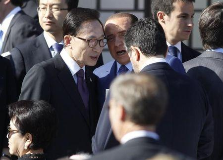 Former South Korean President Lee Myung-bak talks with former Italian Prime Minister Silvio Berlusconi at the dedication for the George W. Bush Presidential Center