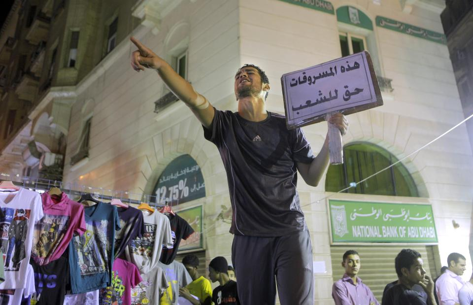 "An Egyptian vendor who sells stolen clothes at a low price calls for clients as he holds an Arabic banner reads "" those theft goods belong to people"" marking Eid el-Fitr holiday, which caps the Muslim fasting month of Ramadan, in Cairo, Egypt late Wednesday, Aug.15, 2012.  (AP Photo/Amr Nabil)"