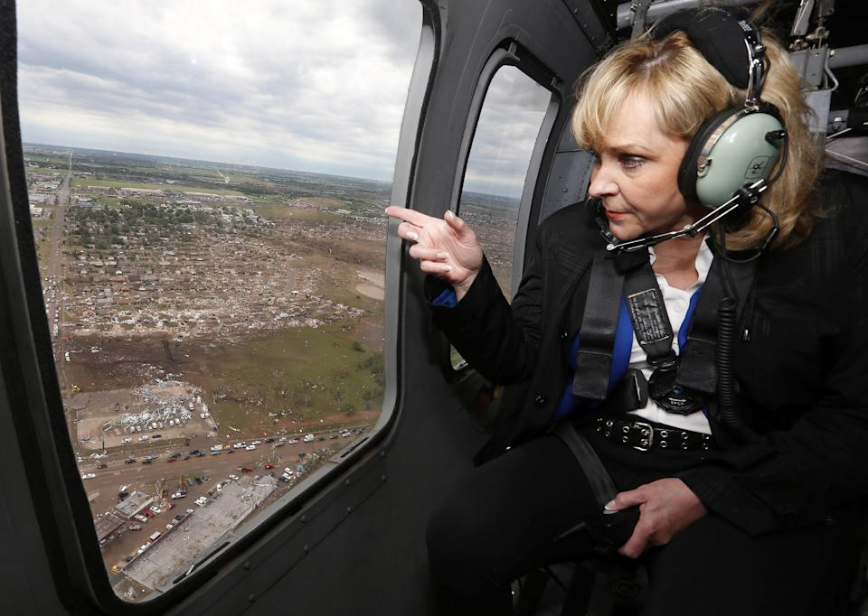 Oklahoma Gov. Mary Fallin looks out the window of a National Guard helicopter as she tours the tornado damage in Moore, Okla., Tuesday, May 21, 2013. (AP Photo/Sue Ogrocki, Pool)