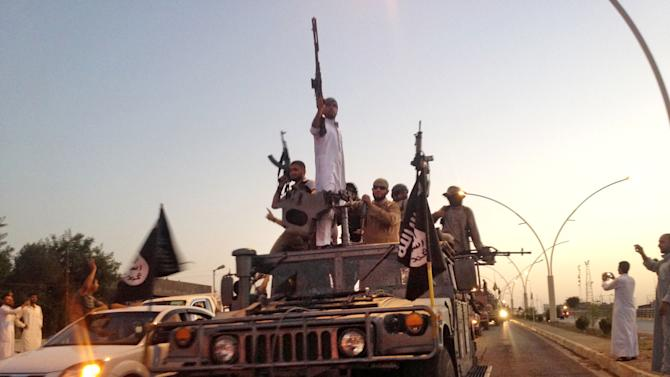 In this Monday, June 23, 2014 file photo, militants from the Islamic State parade down a main street Mosul, Iraq, in a commandeered Iraqi security forces armored vehicle. The chaos unleashed by the Arab Spring has led to the rise of powerful militias -- including many Islamic extremist groups -- across a Middle East where many central governments have been exposed as weak. Some of the groups are allied with such governments, others are fighting to topple them and some -- like the Kurdish peshmerga in northern Iraq -- are seen as vital Western allies. All could prove to be major obstacles to bringing peace or stability to the troubled region. (AP Photo, File)