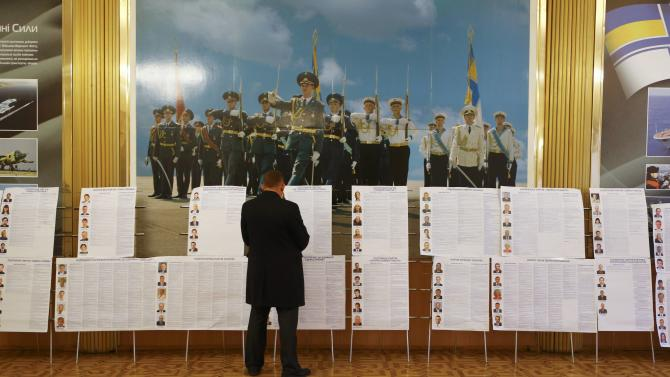 A man stands in front of candidate information sheets during a parliamentary election at a polling station in Kiev