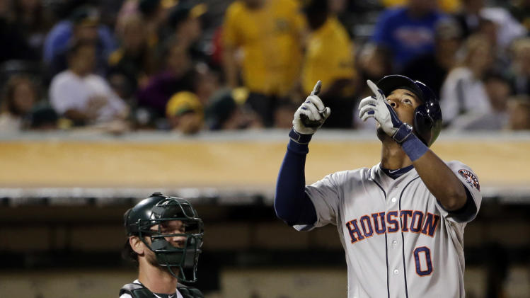 Houston Astros' L.J. Hoes, right, celebrates after his solo home run against the Oakland Athletics during the 12th inning of a baseball game on Tuesday, July 22, 2014, in Oakland, Calif. Houston won 3-2 in 12 innings. (AP Photo)