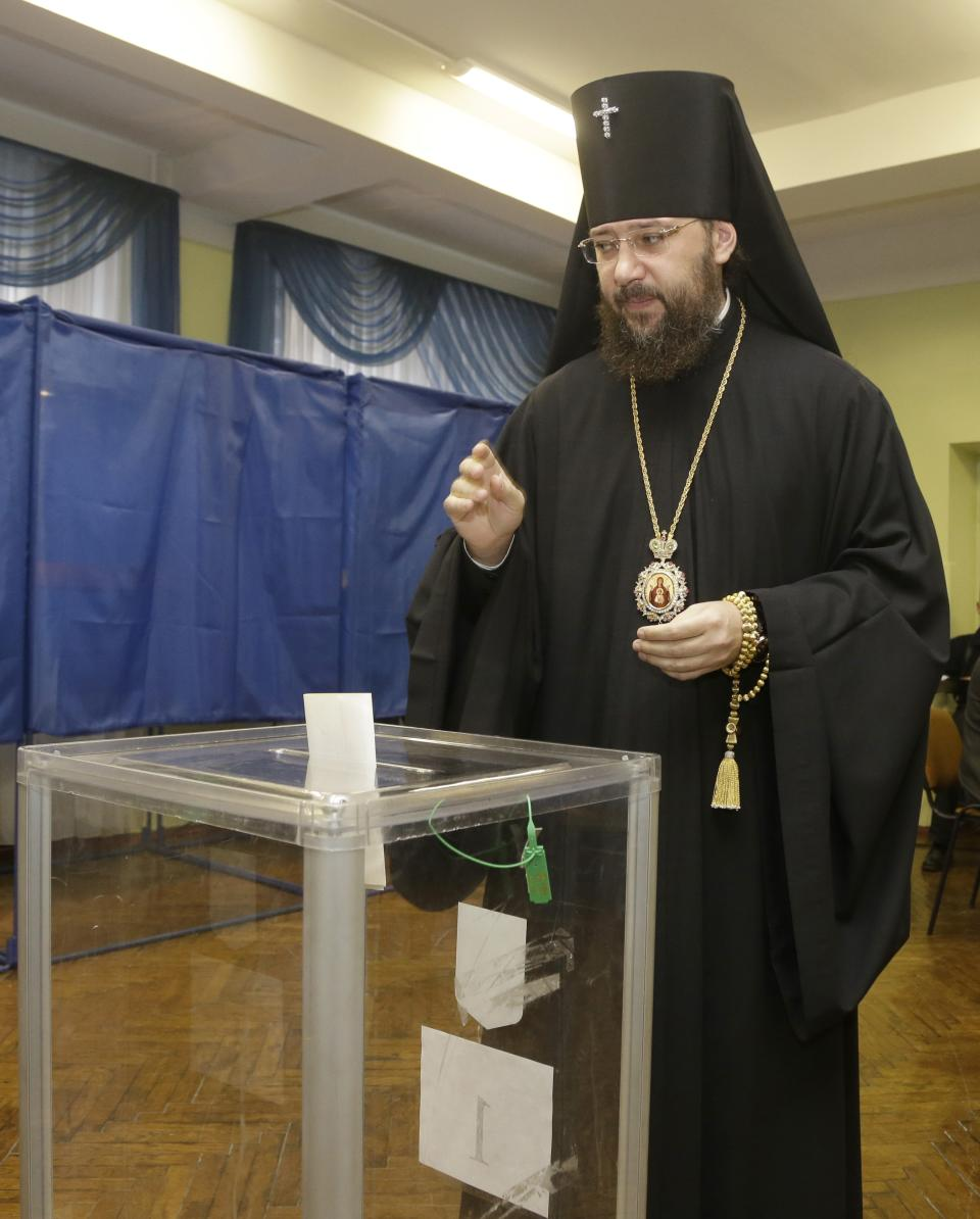 An Orthodox priest blesses his ballot paper at a polling station in Kiev, Ukraine, Sunday, Oct. 28, 2012. Voters in Ukraine are choosing a new parliament Sunday. (AP Photo/Efrem Lukatsky)