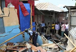 Somali policeman shifts through debris after a blast occurred at a government tax collection point near Kaaraan district north of Mogadishu