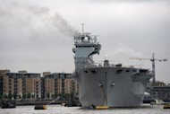 "British Royal Navy helicopter carrier HMS Ocean takes part in security rehearsals, ""Exercise Olympic Guardian"", ahead of the London 2012 Olympic Games on the River Thames in London in May 2012. A security force of more than 40,000 military and civilian personnel, backed by a huge intelligence operation, will turn the British capital into a fortress to protect venues, athletes and visitors"