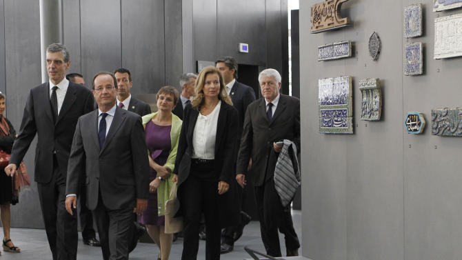French President Francois Hollande, second left, his companion Valerie Trierweiler, second right, Louvre museum president Henri Loyrette, left,  and Sophie Makariou, center behind Hollande, chief of Department of Islamic Arts,  visit the new Department of Islamic Arts galleries at the Louvre museum in Paris, Tuesday Sept. 18, 2012.  (AP Photo/Gonzalo Fuentes, Pool)