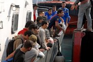A group of Pakistani and Afghan asylum seekers arrive aboard an Indonesian maritime police boat in the port of Banten, in western Java island. Indonesian police have arrested 80 Pakistanis and 17 Afghans stranded after their boat hit a reef as they tried to reach Australia's Christmas Island, an official said Tuesday