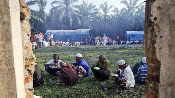 Rohingya migrants have their breakfast at a temporary shelter in Bayeun, Aceh province, Indonesia, Sunday, May 24, 2015. Thousands of migrants - about half of them Bangladeshi and the others minority Rohingya Muslims from Myanmar - have landed ashore in Indonesia, Malaysia and Thailand since May 10. Thousands more are believed to be trapped at sea, and the United Nations has warned that time is running out. (AP Photo/Binsar Bakkara)