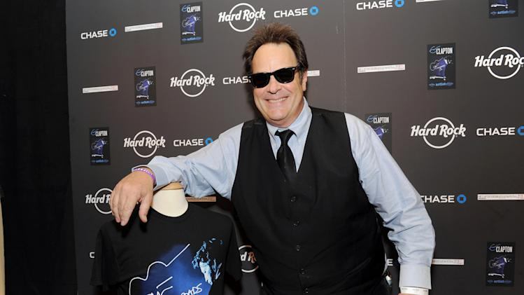IMAGE DISTRIBUTED FOR HARD ROCK INTERNATIONAL - Actor and musician Dan Aykroyd poses with Hard Rock's new limited edition Eric Clapton Artist Spotlight T-Shirt at Eric Clapton's Crossroads Guitar Festival artist party at The Hard Rock Cafe New York on Thursday, April 11, 2013 in New York City, New York. (Photo by Evan Agostini/Invision for Hard Rock International/AP Images)