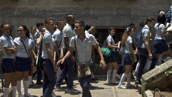 Students come to school for an exam of mathematics at the Pre-University Jose Marti in Old Havana, Cuba, Monday, June 9, 2014. Eight people are under arrest in connection with a scandal involving the illicit sale of university entrance exams, Cuban authorities said Monday, days after thousands of high school students were forced to retake the test. (AP Photo/Franklin Reyes)