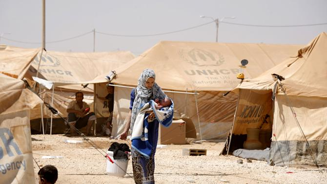 A Syrian refugee woman carries her infant while washes the family clothes at Zaatari refugee camp, in Mafraq, Jordan, Wednesday, Aug. 29, 2012. Jordan's has warned Syrian refugees in its tent camp near the Syrian border against rioting. Public security officials say rioting by 200 refugees late Tuesday over the camp's 'poor services' injured 26 Jordanian security officers.  (AP photo/Mohammad Hannon)