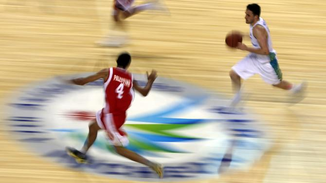 Kazakhstan's Kolesnikov dribbles past Palestinian Younis during their men's basketball qualifying game at Samsan World Gymnasium during the 17th Asian Games in Incheon