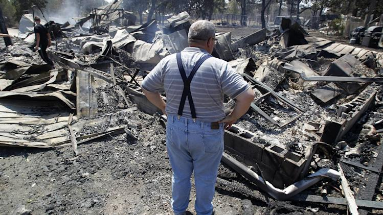 Willie Clements surveys his fire-destroyed home, Tuesday, Sept. 6, 2011, in Bastrop, Texas. Clements lost his home to fires Monday. More than 1,000 homes have burned in at least 57 wildfires across rain-starved Texas, officials said Tuesday. (AP Photo/Eric Gay)